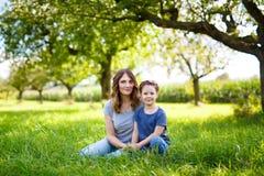 Bella giovane madre e piccola figlia che si siedono sull'erba verde e sul riposo fotografia stock