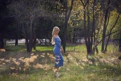 Bella giovane passeggiata bionda della donna nel parco fotografie stock