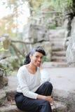 Bella giovane persona femminile nera che si siede nel parco vicino alle scale di pietra ed alla blusa bianca d'uso Fotografia Stock