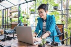 Bella giovane ragazza asiatica che lavora ad una caffetteria con un computer portatile Fotografia Stock