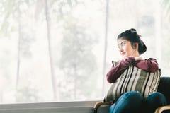Bella giovane ragazza asiatica che si rilassa a casa, sedendosi da solo dalla finestra, esaminante lo spazio della copia fotografia stock