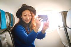Bella giovane ragazza asiatica che si siede confortevolmente sul sedile e che esamina lo smartphone nella cabina e nel sorridere fotografia stock