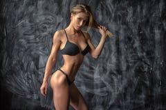 Bella giovane ragazza atletica in biancheria intima su fondo scuro Fotografia Stock