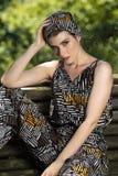 Bella giovane ragazza bionda che posa in un vestito ed in un foulard etnici immagine stock