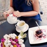 Bella giovane ragazza bionda in vestito da estate alla tavola in pav Fotografia Stock Libera da Diritti