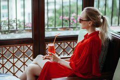 Bella giovane ragazza bionda in vestito ed occhiali da sole rossi che beve cocktail rosso da un vetro su un terrazzo aperto dell' fotografia stock libera da diritti