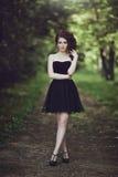 Bella giovane ragazza castana in breve vestito nero che cammina attraverso il legno fotografia stock libera da diritti