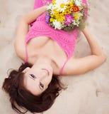 Bella giovane ragazza castana che mette sulla sabbia seaside Holid Fotografia Stock