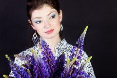 Bella giovane ragazza castana con il prato porpora, fiori a disposizione su un fondo nero nello studio con bello trucco Immagine Stock