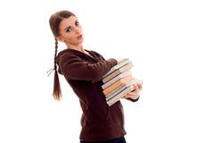 Bella giovane ragazza castana dello studente con molti libri in mani isolate su fondo bianco Fotografie Stock Libere da Diritti
