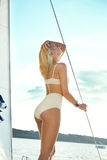 Bella giovane ragazza castana sexy in un vestito e un trucco, viaggio di estate su un yacht con le vele bianche sul mare o oceano Immagini Stock