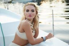 Bella giovane ragazza castana sexy in un vestito e un trucco, viaggio di estate su un yacht con le vele bianche sul mare o oceano Fotografie Stock Libere da Diritti