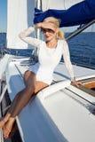 Bella giovane ragazza castana sexy in un vestito e un trucco, viaggio di estate su un yacht con le vele bianche sul mare o oceano Fotografie Stock