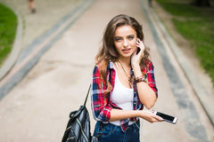 Bella giovane ragazza caucasica felice della High School con lo Smart Phone verde all'aperto su soleggiato Immagini Stock