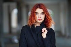 Bella giovane ragazza dai capelli rossi alla moda in un cappotto nero che posa in una stanza abbandonata che guarda direttamente  immagini stock