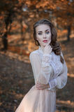 Bella giovane ragazza dai capelli rossi con gli occhi azzurri in un vestito delicato che sta in una foresta negli alberi di autun immagine stock