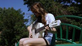 Bella giovane ragazza dei pantaloni a vita bassa che gioca chitarra all'aperto nel parco stock footage