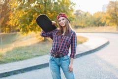 Bella giovane ragazza dei pantaloni a vita bassa in vestiti alla moda che tengono uno skateb Immagini Stock