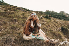 Bella giovane ragazza di boho in rivestimento che si siede su un campo Immagine Stock Libera da Diritti