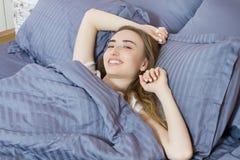 Bella giovane ragazza di sogno che si trova nel suo letto di mattina Salute e bellezza immagini stock