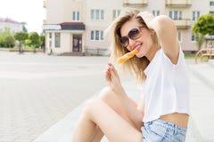 Bella giovane ragazza felice allegra che mangia il gelato, sorridendo in breve e una maglietta bianca sull'area un giorno soleggi fotografie stock libere da diritti