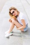 Bella giovane ragazza felice allegra che mangia il gelato, sorridendo in breve e una maglietta bianca sull'area un giorno soleggi immagine stock libera da diritti