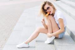 Bella giovane ragazza felice allegra che mangia il gelato, sorridendo in breve e una maglietta bianca sull'area un giorno soleggi fotografia stock