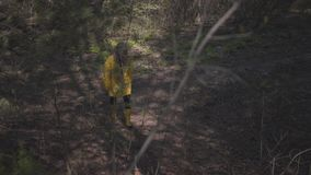 Bella giovane ragazza felice in un impermeabile giallo e nelle passeggiate gialle degli stivali di gomma sulla natura La ragazza  video d archivio