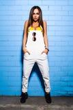 Bella giovane ragazza sexy dei pantaloni a vita bassa che posa e che sorride vicino al fondo blu urbano della parete in costume d Fotografia Stock Libera da Diritti