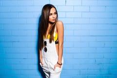 Bella giovane ragazza sexy dei pantaloni a vita bassa che posa e che sorride vicino al fondo blu urbano della parete in costume d Fotografia Stock