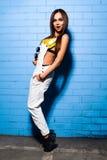 Bella giovane ragazza sexy dei pantaloni a vita bassa che posa e che sorride vicino al fondo blu urbano della parete in costume d Fotografie Stock Libere da Diritti