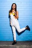 Bella giovane ragazza sexy dei pantaloni a vita bassa che posa e che sorride vicino al fondo blu urbano della parete in costume d Fotografie Stock