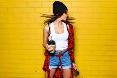 Bella giovane ragazza sexy dei pantaloni a vita bassa con il caffè scorrente della bevanda dei capelli, sorridendo e posando vici Immagini Stock