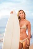 Bella giovane ragazza sexy del surfista in bikini sulla spiaggia a sunse Fotografia Stock