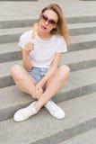 Bella giovane ragazza sexy in occhiali da sole che mangia il gelato sulla scala e che lecca le labbra grassottelle un il giorno c immagini stock libere da diritti