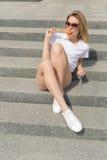 Bella giovane ragazza sexy in occhiali da sole che mangia il gelato sulla scala e che lecca le labbra grassottelle un il giorno c fotografia stock