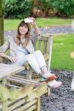 Bella giovane ragazza studient felice con lo Smart Phone bianco all'aperto in vacanza fa il selfie e sorridere Fotografia Stock