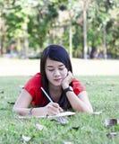 Bella giovane scrittura castana della donna in suo diario Immagini Stock Libere da Diritti