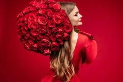 Bella giovane signora castana nel rosso con il mazzo di rose rosse sulla spalla fotografia stock libera da diritti