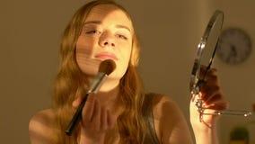 Bella giovane signora che applica la polvere della pelle, mettendo trucco, preparante per il partito archivi video