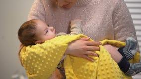 Bella giovane signora che canta poco bambino per dormire, tenendo con attenzione nelle armi archivi video