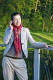 Bella giovane signora che comunica sopra il telefono mobile Immagini Stock