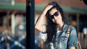 Bella giovane signora che porta il rivestimento alla moda dei jeans con capelli lunghi che posano in caffè al tramonto video d archivio