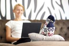 Bella giovane signora che si siede sul sofà, per mezzo del computer portatile fotografie stock libere da diritti