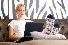 Bella giovane signora che si siede sul sofà, per mezzo del computer portatile fotografia stock