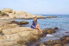 Bella giovane signora che si siede sulla pietra enorme vicino al tu Immagine Stock Libera da Diritti