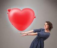 Giovane signora che tiene il cuore adorabile di rosso 3d Fotografia Stock