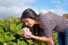 Bella giovane signora Smells The Flower Immagini Stock