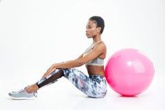 Bella giovane sportiva afroamericana che si siede e che posa con il fitball Immagini Stock Libere da Diritti