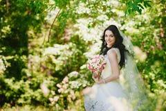 Bella giovane sposa castana felice all'aperto in vestito da sposa, acconciatura, trucco, nozze, stile di vita Immagini Stock